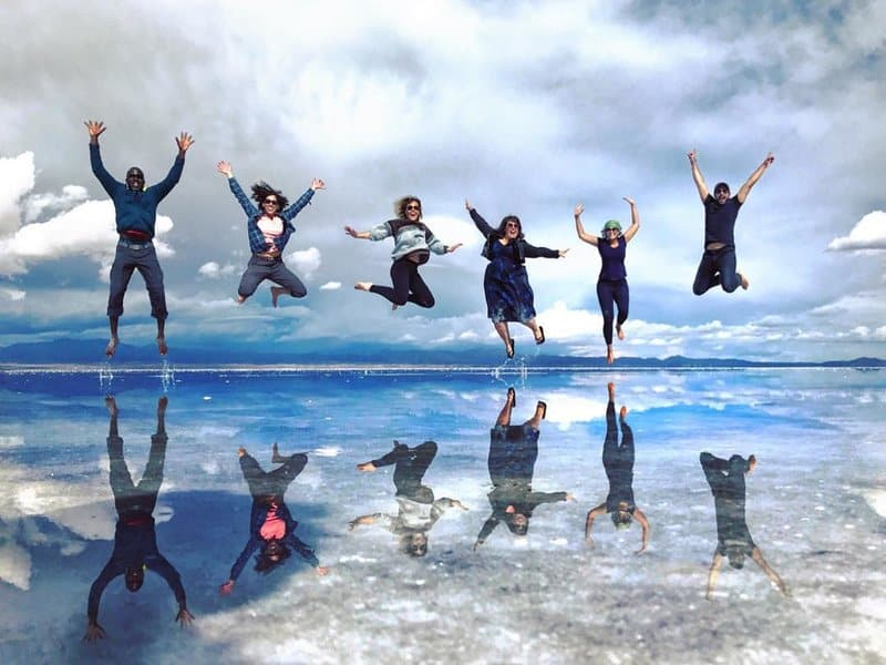 Group of travelers jumping at Bolivian salt flats after journey from Cusco to Uyuni